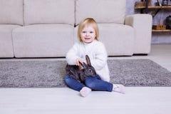 逗人喜爱的小女孩用灰色复活节兔子,兔宝宝 微笑在白色毛线衣和蓝色牛仔裤的白肤金发的女婴在家坐c 库存图片