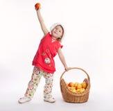 逗人喜爱的小女孩用苹果和篮子 免版税库存照片