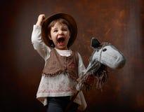 逗人喜爱的小女孩穿戴了象使用与自创h的牛仔 库存图片
