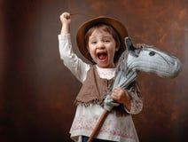 逗人喜爱的小女孩穿戴了象使用与自创h的牛仔 免版税库存图片