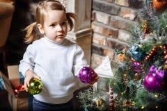 逗人喜爱的小女孩美丽的照片在家装饰圣诞树的2年 免版税库存照片