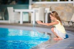 逗人喜爱的小女孩获得与飞溅的乐趣在游泳池附近 免版税库存图片