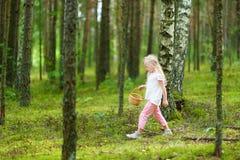 逗人喜爱的小女孩获得乐趣在森林远足期间在美好的夏日 免版税库存照片
