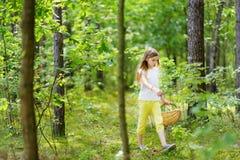 逗人喜爱的小女孩获得乐趣在森林远足期间在美好的夏日 库存照片