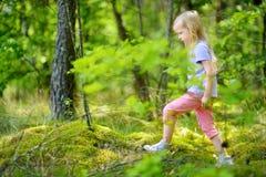 逗人喜爱的小女孩获得乐趣在森林远足期间在美好的夏日 免版税图库摄影