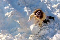逗人喜爱的小女孩获得乐趣在降雪 户外儿童游戏在雪的冬天季节 库存图片