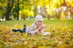逗人喜爱的小女孩读一本书,当放置在黄色秋叶时 免版税库存照片