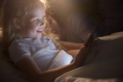 逗人喜爱的小女孩读书E书在床上 库存照片