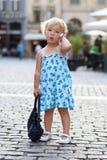 逗人喜爱的小女孩谈话在手机在城市 免版税库存图片