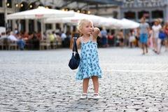 逗人喜爱的小女孩谈话在手机在城市 免版税图库摄影