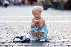 逗人喜爱的小女孩谈话在手机在城市 库存图片
