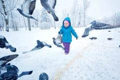 逗人喜爱的小女孩赛跑和吓唬鸽子 免版税库存图片