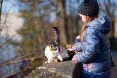 逗人喜爱的小女孩遇见了一只猫户外 免版税库存图片