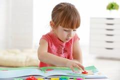 逗人喜爱的小女孩阅读书在讲话办公室 库存图片