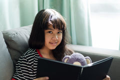 逗人喜爱的小女孩阅读书在家她的玩偶,软的焦点sho 库存图片