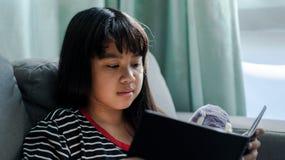 逗人喜爱的小女孩阅读书她的玩偶在家 库存照片