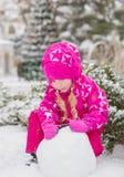 逗人喜爱的小女孩雕刻雪人 库存图片