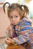 逗人喜爱的小女孩饮用的汁液 免版税库存图片
