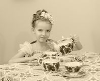逗人喜爱的小女孩饮用的茶在老桌上 免版税库存照片