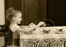 逗人喜爱的小女孩饮用的茶在老桌上 免版税库存图片