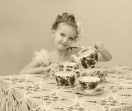 逗人喜爱的小女孩饮用的茶在老桌上 库存照片