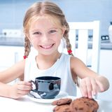 逗人喜爱的小女孩饮用的茶用曲奇饼 免版税库存图片
