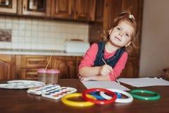 逗人喜爱的小女孩,与水彩的可爱的学龄前儿童绘画 免版税库存照片