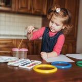 逗人喜爱的小女孩,与水彩的可爱的学龄前儿童绘画 库存照片