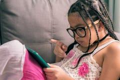 逗人喜爱的小女孩,在家使用与放置在沙发的计算机 库存图片