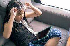 逗人喜爱的小女孩,在家使用与放置在沙发的计算机 免版税图库摄影