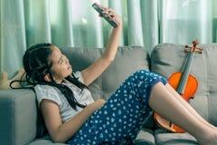 逗人喜爱的小女孩,在家使用与放置在沙发的计算机 免版税库存照片
