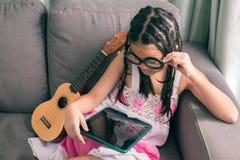 逗人喜爱的小女孩,在家使用与放置在沙发的计算机 图库摄影
