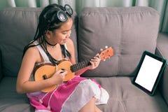 逗人喜爱的小女孩,在家使用与放置在沙发的计算机 库存照片