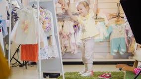 逗人喜爱的小女孩满意对在儿童` s服装店的新的衣裳 免版税图库摄影