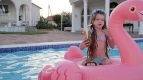 逗人喜爱的小女孩给漂浮在水池,儿童饮料甜饮料的空气亲吻坐可膨胀的火鸟,富有 影视素材