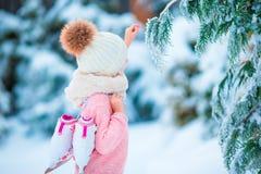逗人喜爱的小女孩去的冰鞋在冬天雪天户外 免版税图库摄影