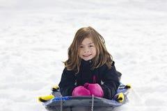 逗人喜爱的小女孩去的雪sledding在小山下 免版税图库摄影