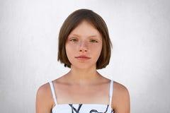 逗人喜爱的小女孩以短的黑暗浮动了头发、褐色宽光亮的眼睛、稀薄的嘴唇和有雀斑的皮肤佩带的白色夏天礼服神色 库存照片