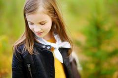 逗人喜爱的小女孩画象在城市公园的秋天天 库存照片