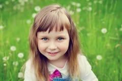 逗人喜爱的小女孩画象有美好的微笑和蓝眼睛的坐花草甸,愉快的童年 免版税库存图片