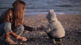 逗人喜爱的小孩和母亲一起花费时间并且寻找,采摘并且收集海壳在沙滩 影视素材