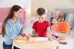 逗人喜爱的小孩图画在与少妇的桌上 免版税库存照片