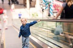 逗人喜爱的小孩在站立在移动的自动扶梯的购物中心 免版税库存图片