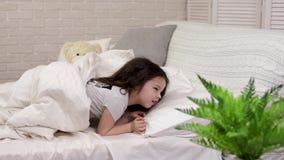逗人喜爱的小孩女孩从睡眠在床上醒 股票录像