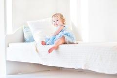 逗人喜爱的小孩女孩在家坐一张白色床 免版税库存照片