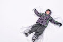 逗人喜爱的小孩男孩在五颜六色的冬天给做雪天使穿衣 库存照片