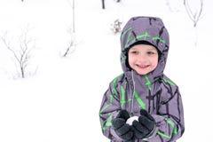 逗人喜爱的小孩男孩在五颜六色的冬天给做雪天使穿衣 免版税图库摄影