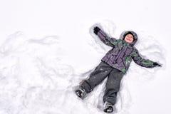 逗人喜爱的小孩男孩在五颜六色的冬天给做雪天使穿衣 免版税库存图片