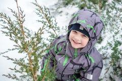 逗人喜爱的小孩男孩在五颜六色的冬天给放下穿衣  与孩子的户外激活休闲 愉快的子项 免版税库存图片