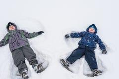 逗人喜爱的小孩男孩在五颜六色的冬天给放下穿衣  与孩子的户外激活休闲 愉快的子项 库存图片